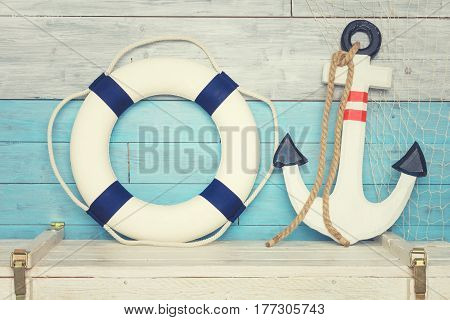 Anchor and lifeline against the background of blue-white boards. Coloseup