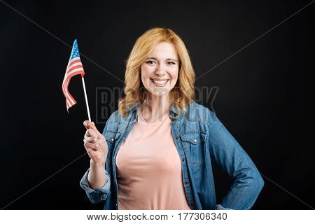 Good souvenir. Good looking female wearing casual clothes keeping smile on face while holding American flag in right hand