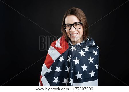 Now I am happy. Positive delighted female wearing glasses keeping smile on her face while standing over black background