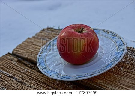 Red apple on a white plate standing on a piece of wood