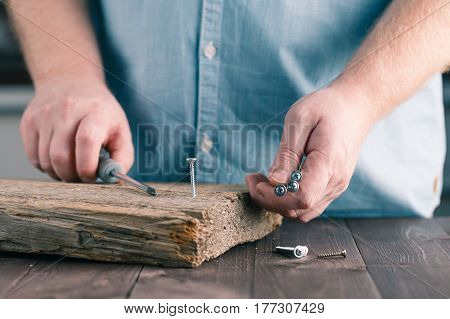 Screwing A Screw Into Wood With A Screwdriver