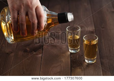 Pouring Alcohol In Shot Glass On Wooden Table