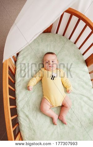 Portrait of cute funny adorable white Caucasian little baby newborn in yellow onesie lying in crib alone near window lifestyle candid real life view from top above