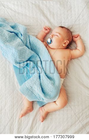 Portrait of a cute adorable white Caucasian baby newborn in diaper sleeping dreaming with pacifier soother in mouth lying on bed covered with blue blanket view from top above
