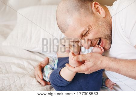 Funny portrait of middle age Caucasian father in white t-shirt lying in bed with newborn baby son kissing biting his feet toes parenting childhood bonding concept lifestyle