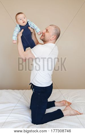 Portrait of middle age Caucasian father in white t-shirt and black jeans sitting on bed indoors holding taking up newborn baby son making him laugh funny touching real lifestyle