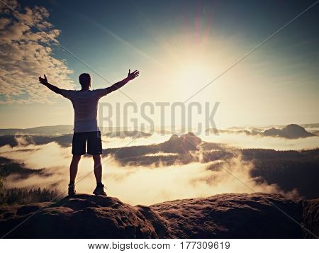 Happy Man Gesture Of Triumph With Rams In Air On Rock Summit