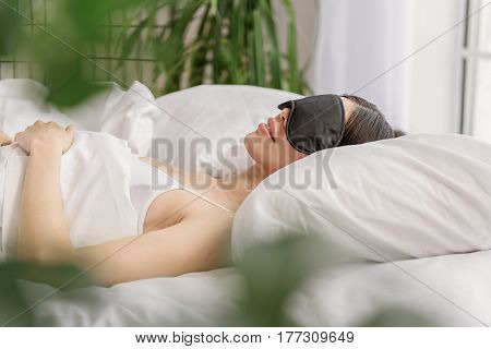 Smiling woman with eye mask having good dreams while sleeping in bed. Concept of satisfaction