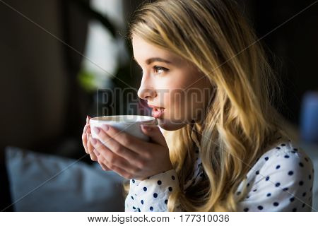 Portrait Of Young Gorgeous Female Drinking Tea And Thoughtfully Looking Out Of The Coffee Shop Windo