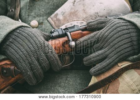 Close up of German military ammunition of a German soldier at World War II. Warm autumn clothes, soldier's overcoat, gloves, helmet, sapper shovel, rifle.