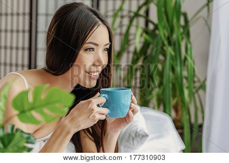 Pleased asian woman tasting hot beverage while looking away. Enjoyment concept