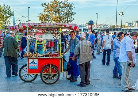 ISTANBUL, TURKEY - SEPTEMBER 26: Chestnuts seller and passers-by in the square in front of the New Mosque, Yeni Cami in the Eminonu district on September 26th, 2013 Istanbul, Turkey.