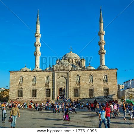 ISTANBUL, TURKEY - SEPTEMBER 26: Tourists and passers-by in the square in front of the New Mosque, Yeni Cami, in the Eminonu district on September 26th, 2013 Istanbul, Turkey.