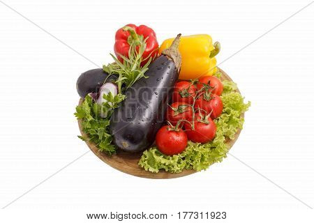 Red yellow paprika of a paprika tomatoes and eggplants on a round wooden board. Healthy food food subject. Top view