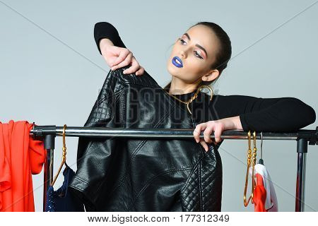 Pretty young woman slim fashion model with sexy blue lips in bodysuit posing with clothing and black leather jacket on hangers at clothes rack wardrobe on grey background