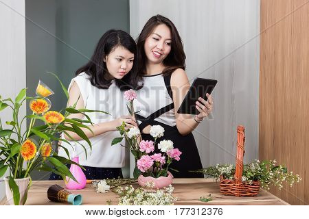 Young mother and teenage daughter using digital tablet while putting beautiful flowers into a vase and see preview of Internet on tablet the concept of lifestyle and leisure activity within the family