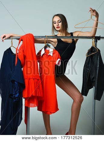 Pretty sexy young woman slim fashion model with red lips in black bodysuit posing with hanger at clothes rack wardrobe of colorful clothing on grey background