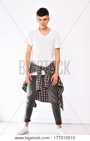handsome stylish man young caucasian guy with serious face in fashionable grey pants tshirt and checkered plaid shirt isolated on white background