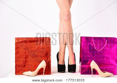 sexy female long legs in fashionable shoes with pink and orange shopping bags packages isolated on white background copy space