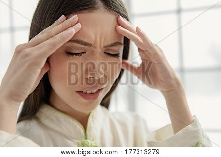 Focus on portrait of face of disappointing asian woman expressing pain. She is touching her head