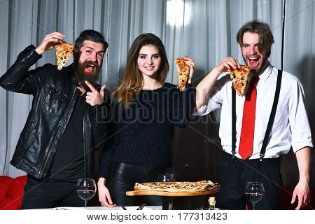 Happy friends pretty girl and two bearded men hipsters with beards eating tasty pizza slices with thumbs up gestures at party in pizzeria cafe or restaurant