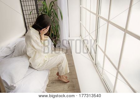 Yong female crying while closing face by arms in bedroom. Upset concept