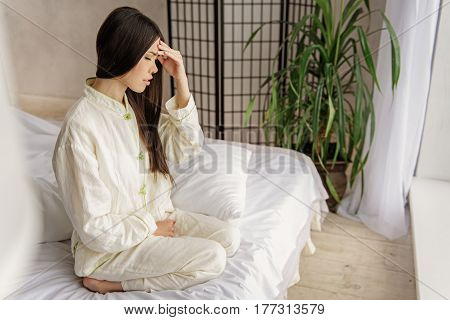 Side view of profile of young female expressing poor health while sitting on bed. Unwellness concept
