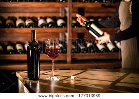 Glass of red wine and a bottle place on a table. Sommelier holding a bottle of wine and standing next to the shelves with wine bottles.