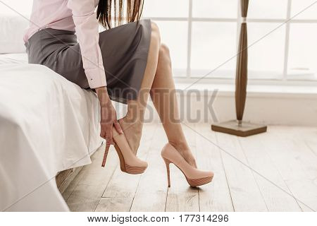 Attractive young female putting on her shoes while sitting on bed in room. Close up of her legs