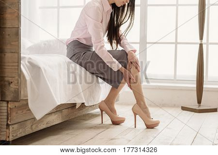My legs are aching after working hours. Tired woman keeping legs while sitting in bedroom after returning home from job