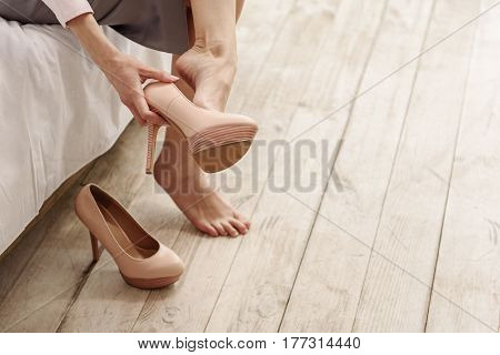 Tired woman taking shoes off after long hours spending on job. Fatigue concept. Close up of her legs