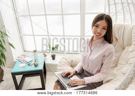 Portrait of delighted young female laboring on notebook computer while situating on chair
