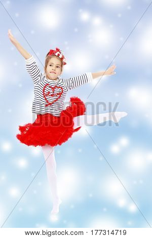 Little girl in a red skirt and bow on her head.She poses with her arms out to the side and pulling to the side of the leg.Blue Christmas festive background with white snowflakes.