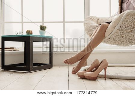 Frazzle woman situating on comfortable seat after job. Tired concept. Close up of her legs near shoes on high heels