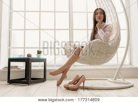 Pensive young female resting in cozy chair after working hours in office. Rest concept