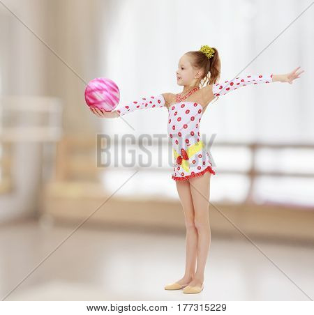 Cute little girl gymnast in a beautiful costume for competition, performs exercises with the ball.In the sports hall with mirror and a large semi-circular window.