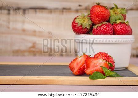 Fresh strawberries in bowl on slate. Healthy food