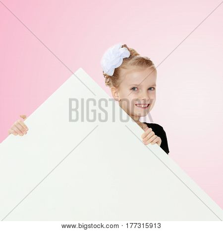 Beautiful little blonde girl dressed in a white short dress with black sleeves and a black belt.The girl peeks out from behind white banner.Close-up.Pale pink gradient background.