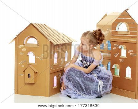 Adorable little blond girl dressed in long Princess dress.Girl posing near a house made of cardboard.Isolated on white background.