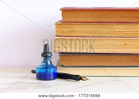 Vintage bottle of ink and pen sits in front of a stack of vintage books with room for copy.