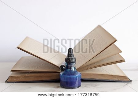 Vintage book open with fanned pages and a bottle of ink and pen in foreground. Room for copy.