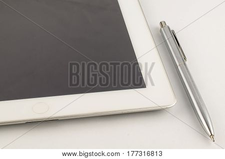 Tablet Pc And A Modern Metal Pen On A White Background.