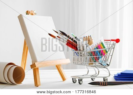 Mini shopping cart full with artistic goods for drawing artist canvas and easel. Art shop concept.