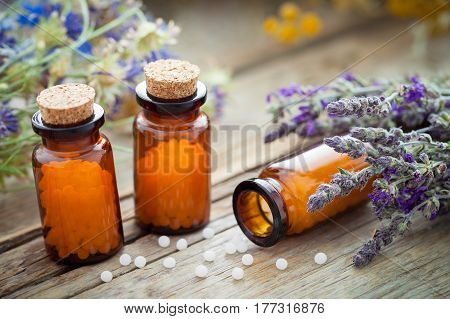 Bottles of homeopathic globules and healing herbs on wooden board. Homeopathy medicine.