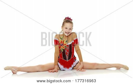 Beautiful little girl gymnast dressed in sports suits for competition, performs the splits.Isolated on white background.