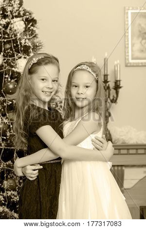 Adorable little twin girls hugging each other near the Christmas tree.Black-and-white photo. Retro style.
