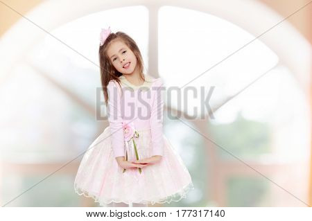 Dressy little girl long blonde hair, beautiful pink dress and a rose in her hair.She folded their hands in front of him.In a room with a large semi-circular window.