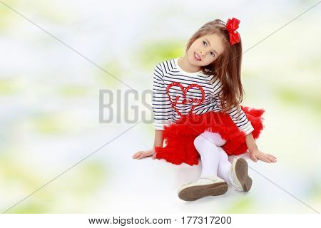 Portrait of a little girl in a bright red skirt with a red bow on his head.The girl sat down legs.Summer white green blurred background.
