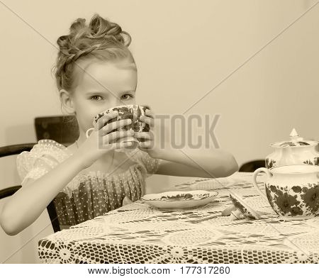 Beautiful little girl Princess , sitting at an antique table with a lace tablecloth and drinking tea.She holds the mug up to his mouth.Black-and-white photo.
