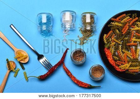 Colorful Dried Fusilli Pasta And Salt Crystals On Black Plate